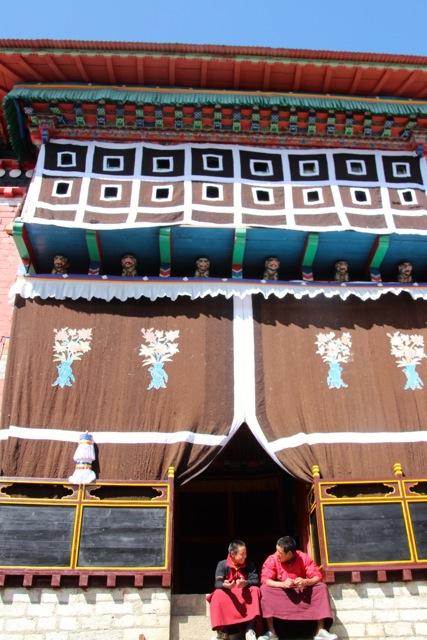 Mönche sitzen in Tengboche vor dem Kloster