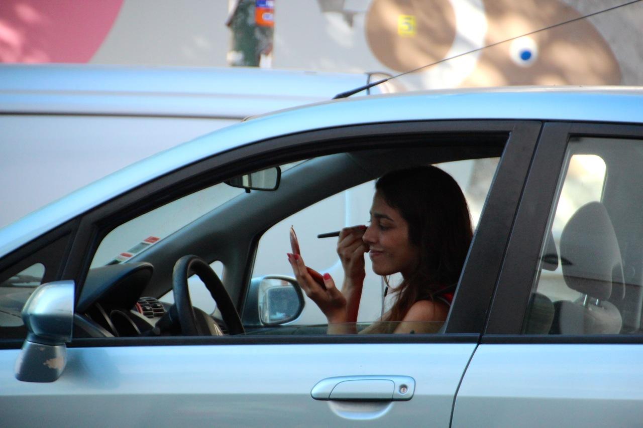 eine Frau schminkt sich im Auto