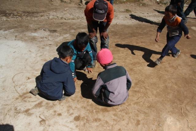 Kinderspiel: Münzen werden auf ein Loch geworfen