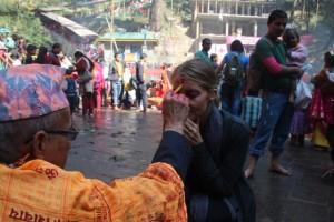 Ein Priester malt uns eine Tilaka auf die Stirn