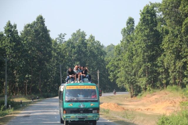 Passagiere in Nepal sitzen of auf den Bussen