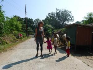 neugierige Kinder nehmen im Dorf Susanne an die Hand